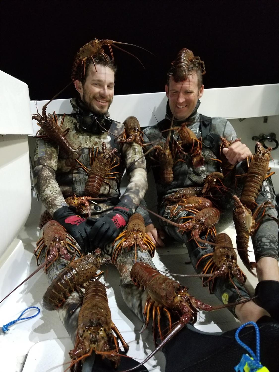 2 men covered in lobsters after diving