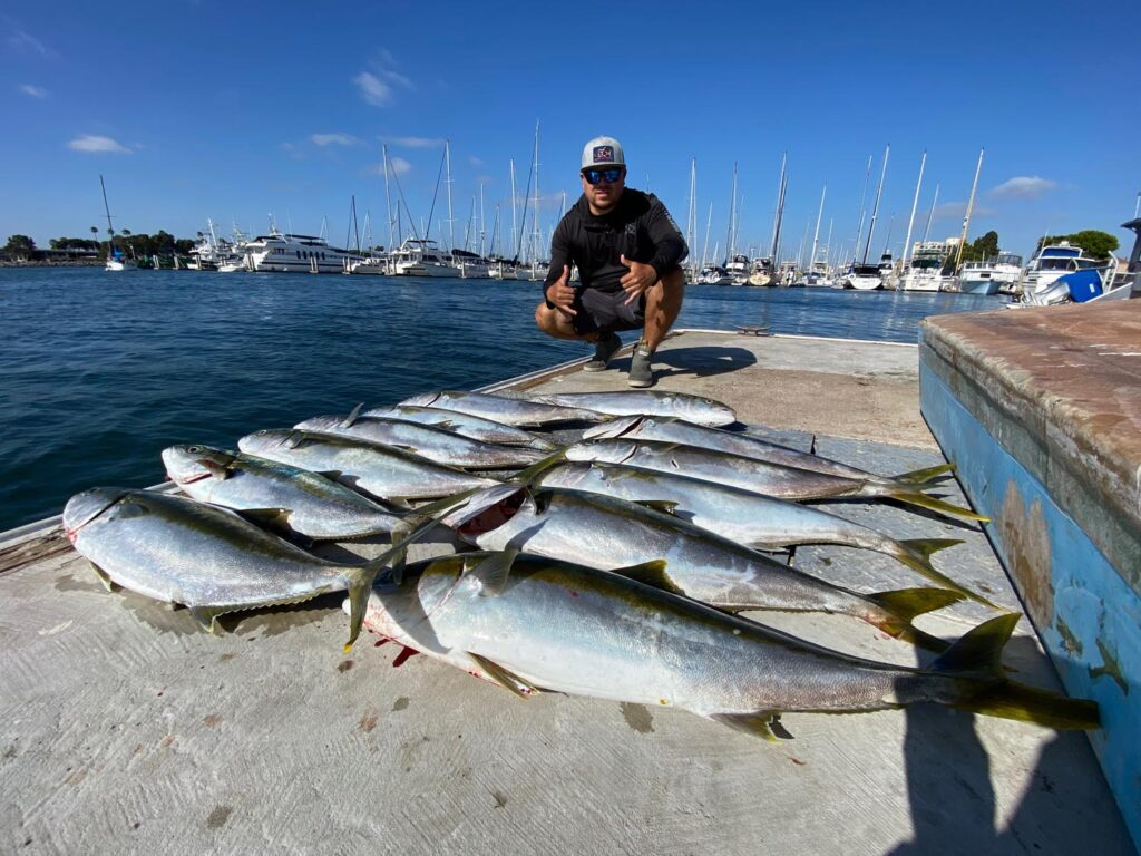Man standing with fish caught on fishing charter